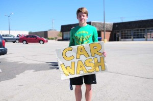 Holding up a sign for the soccer car wash, sophomore Joe Stokes tries to get attention from the passing cars on the busy street. Stokes was on junior varsity this year.