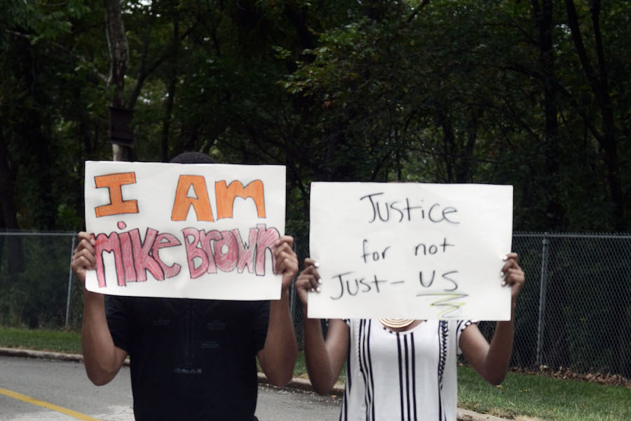 From left: junior Remy Gordon and senior Corida Cooperwood stand in solidarity with Ferguson, protesting the death of Michael Brown.