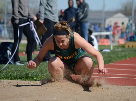Jumping into the sand pit with her jumping spikes, senior Gretchen Fiebig tackles her triple jump event at South Relays.