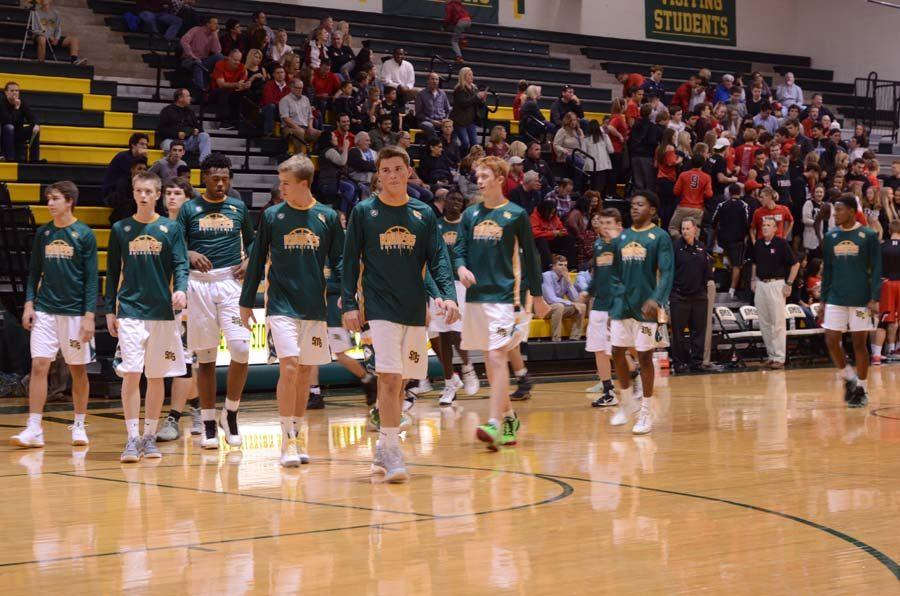 Varsity+basketball+players+in+their+green%2C+gold+and+white+make+their+entrance.+The+first+game+was++Dec.+2%2C+2016+against+Blue+Valley+West+47-36.+