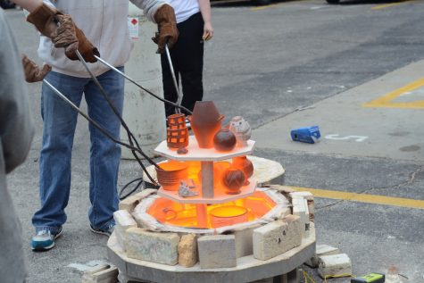 After being postponed students finally get to enjoy Raku Day. A student grabs a piece of pottery from the kiln.