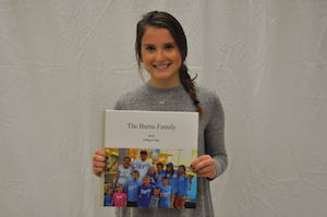 Junior Sydney Burns holding up a picture of her family.