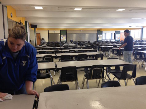 A student helps a teacher clean the tables after lunch.