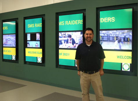 Administrator Nicholas Platko stands next to the new TV screens added to the front hall over the summer. There has been talk of plans to add more screens in different places throughout the school in the future.  Photo By Cassandra Awad
