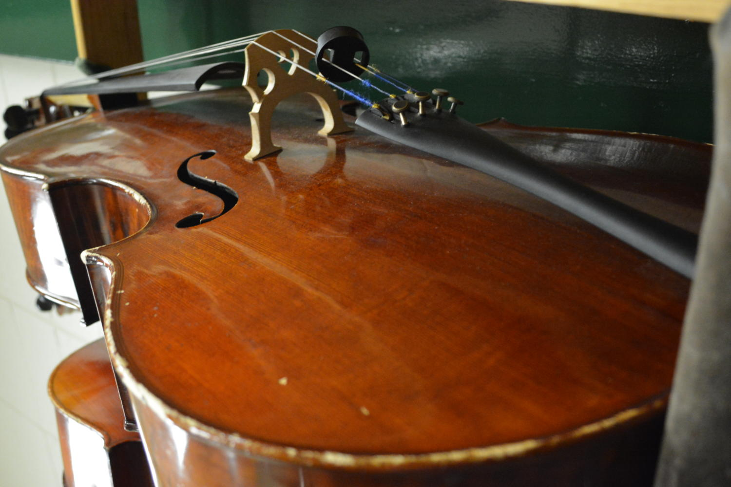 A student's cello is being stored in the instrument room in the Orchestra class. During most other hours this instrument would have been out and playing beautiful music.